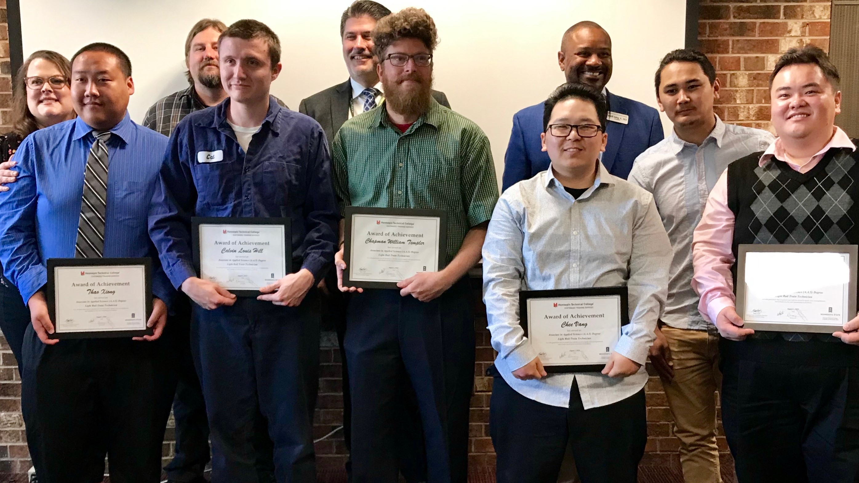 Six LRT train technicians receive certificates of completion in a ceremony Aug. 2, 2019, at Hennepin Technical College where they earned associate degrees. From the left in the front row, they are: Thao Xiong, Calvin Hill, Chapman Templer, Chee Vang, Tenzin Kunga and Toua Yang.