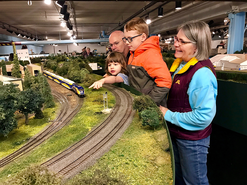 Maria Dierks of Elk River and her grandchildren admire miniature Northstar commuter rail operations and maintenance facility in Big Lake, Minn.