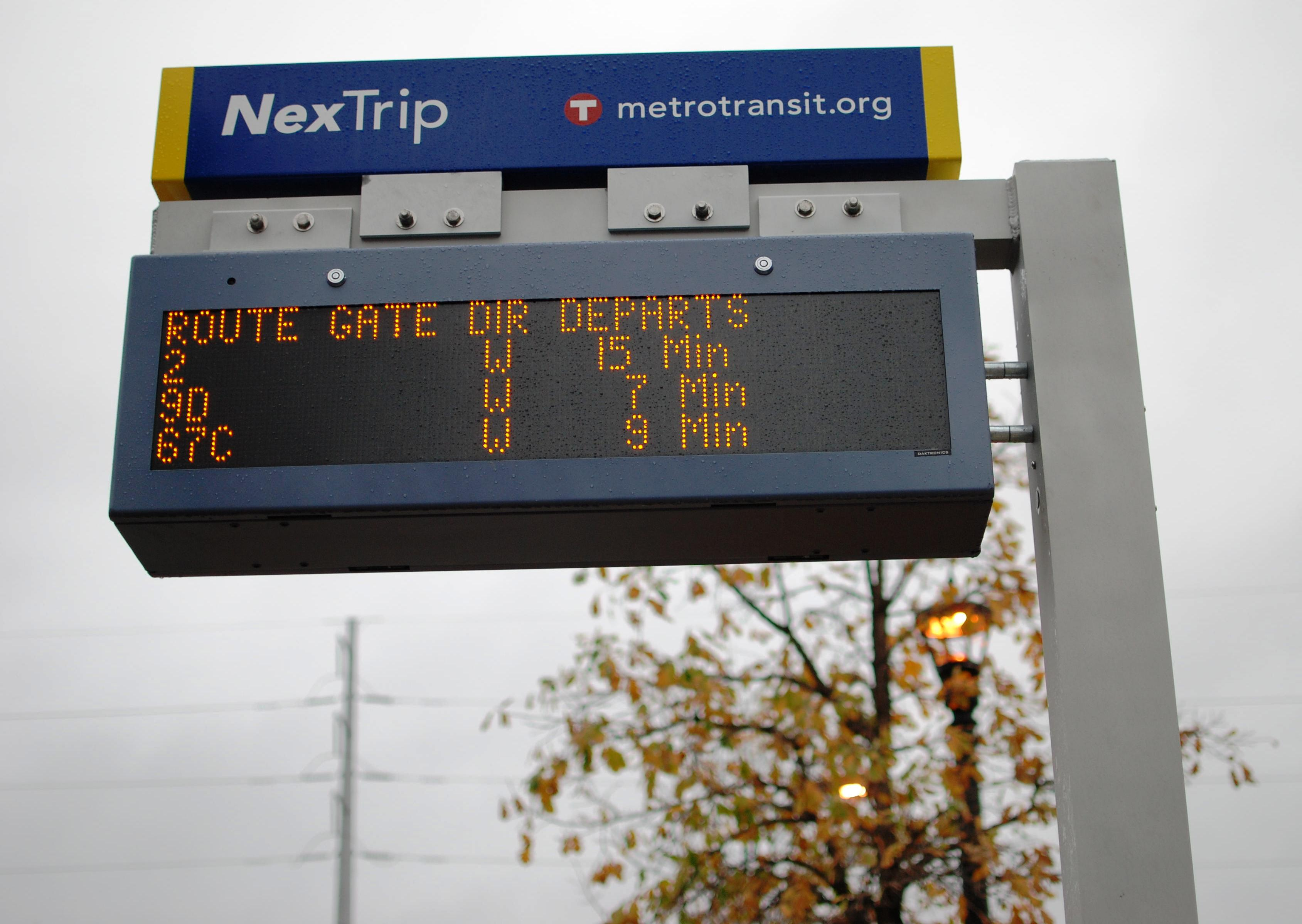A NexTrip sign provides expected real-time departures for upcoming bus trips. The sign posts also have a button for audio information.