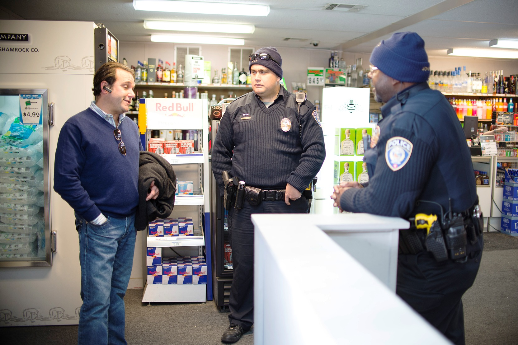 Metro Transit police officers David Hutchinson and Sidney Jones talk with Dean Rose, who owns Broadway Liqour Store at the corner of Broadway and Penn avenues.
