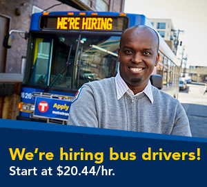 Bus driver standing in front of bus themed with hiring drivers.